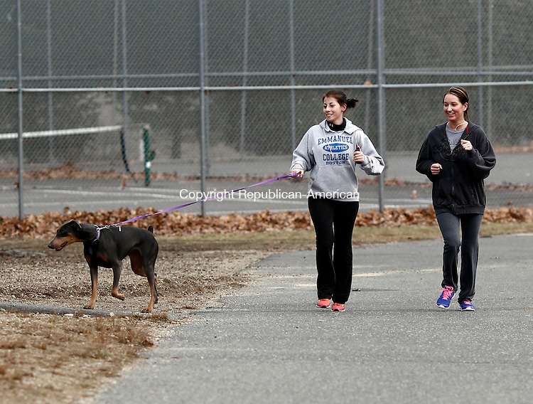 Naugatuck, CT- 13 January 2014-011314CM03- Kailey O'Brien, left, of Watertown, runs with Nova, a Doberman, puppy along with Sarah Bulakites, of Naugatuck around Baumer's Pond in Naugatuck Monday afternoon.  Area residents were seen jogging and walking around the pond after mild weather was felt in the area.  According to the National Weather Service, Tuesday is expected to see rain, with the temperature reaching the mid 40's.     Christopher Massa Republican-American