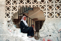 A Palestinian woman with her son is seen through a hole made by Israeli soldiers at her house in the destroyed center of Jenin refugee camp in the northern West Bank Friday, April 19, 2002. Residents of the camp continue to salvage belongings and bury bodies following the Israeli military assault that begin on April 3. Photo by Quique Kierszenbaum