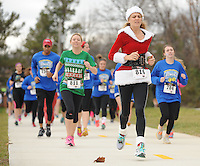 STAFF PHOTO ANDY SHUPE - Lynda Hurst of West Fork, right, runs during the Jingle Bell Run/Walk for Arthritis Sunday, Dec. 14, 2014, at Lake Fayetteville Park in Fayetteville. The event featured a 5-kilometer run, a 1-mile walk and a tot-trot for children to support the Arthritis Foundation.