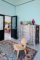 A converted shoe factory blends old world flavour with warehouse edge. In a sitting corner an Eames chair stands on a vintage rug with a decorated chest of drawers behind.