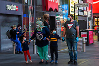 NEW YORK, NY - MAY 27: A man and woman with two children wearing face masks and latex gloves walk through Times Square on May 27, 2020 in New York City. Some Times Square billboards went off for a minute in gratitude to the millions of medical workers and essential workers who have given their lives to fight the COVID-19 pandemic. The number of deaths from this pandemic exceeded 100,000 in the United States. (Photo by Pablo Monsalve / VIEWpress via Getty Images)