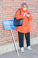 A woman stands next to a Warren campaign sign before Democratic presidential candidate and Massachusetts senator Elizabeth Warren held a small rally outside Graham & Parks School after the candidate voted in the Massachusetts primary as part of Super Tuesday voting in Cambridge, Massachusetts, on Tue., March 3, 2020. The polling place is just a few blocks from Warren's residence. Polls show Warren and Vermont senator Bernie Sanders in a near tie in the Massachusetts Democratic party primary.