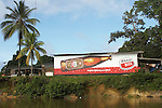 The Marowijne River, Suriname.  Parbo beer advertisement on the side of a building along the river.