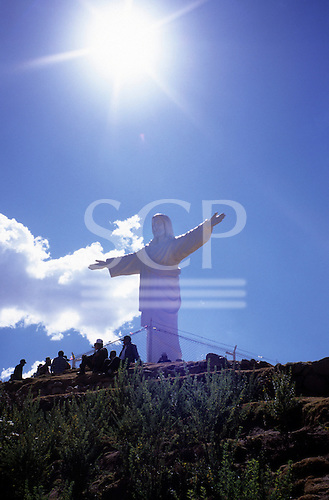 Cusco, Peru. Christ statue near Sacsayhuaman above Cusco with sunburst above and people sitting in foreground.