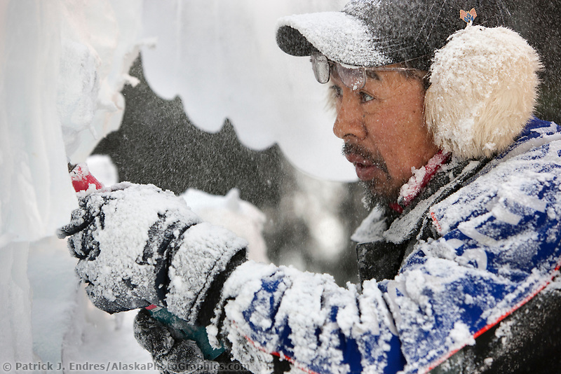"Japanese ice sculptor Junichi Nakamura, carves away on a single block, realistic sculpture titled ""Surfacing Kingfisher"" during the 2009 World Ice Art Championships in Fairbanks, Alaska."
