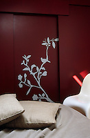 An adhesive silhouette of a branch adorns a sliding door in this burgundy-coloured bedroom