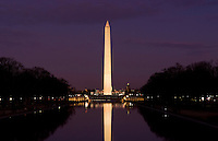 Beautiful tall tower of the Washington Monument and pond with capital building at night after sunset in Washington DC USA