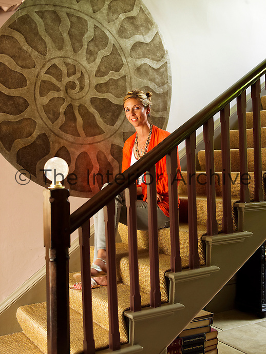 Georgie Leatham sitting on the stairs of her Wiltshire house
