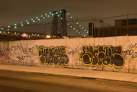 Williamsburg, Brooklyn, New York City, New York State, USA....Cityscape at Night, Street, Sidewalk, Metal Wall with Graffiti, Williamsburg Bridge in the distance