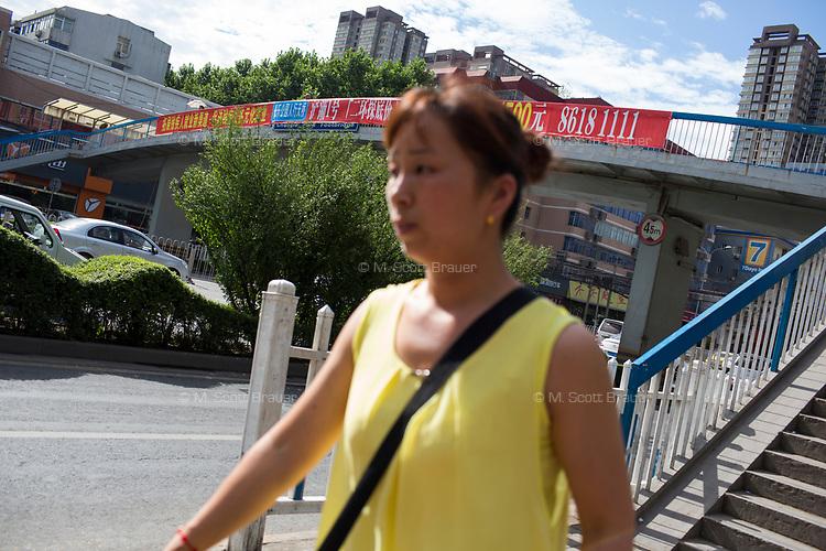 A woman walks near a pedestrian overpass in Xian, Shaanxi, China.