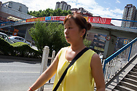 A woman walks near a pedestrian overpass in Xian, Shaanxi, China.