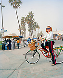 USA, California, Los Angeles, Venice Beach, a hip young woman strikes a pose with her bike on the Venice Beach Boardwalk
