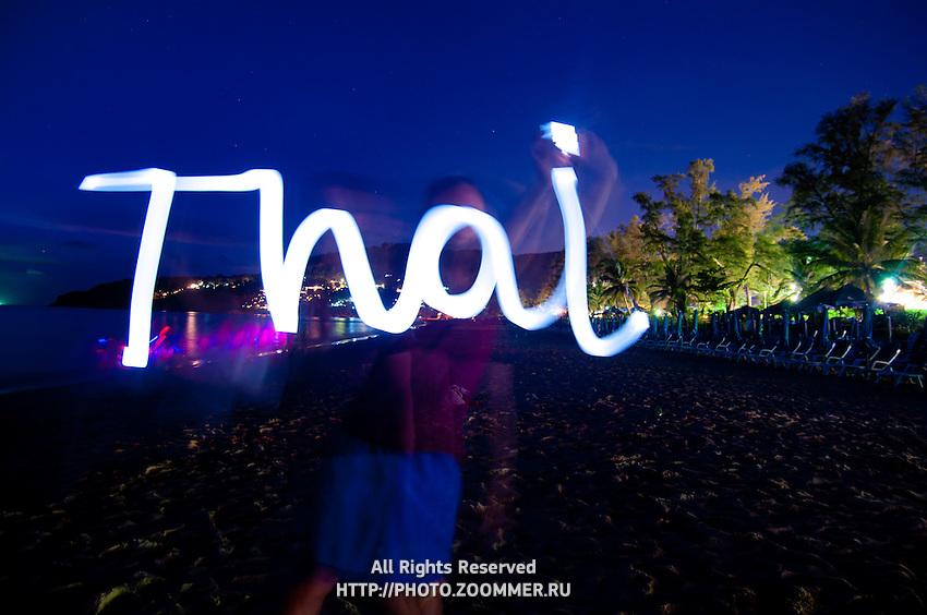 Man lightpaints the word Thai, Phuket, Thailand