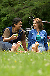 Couple barefoot  and chatting  in meadow with bikes