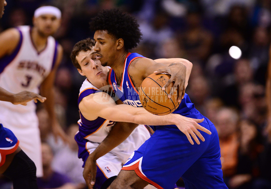 Jan. 2, 2013; Phoenix, AZ, USA: Philadelphia 76ers guard Nick Young (right) controls the ball under pressure from Phoenix Suns guard Goran Dragic in the second half at the US Airways Center. The Suns defeated the 76ers 95-89. Mandatory Credit: Mark J. Rebilas-USA TODAY Sports