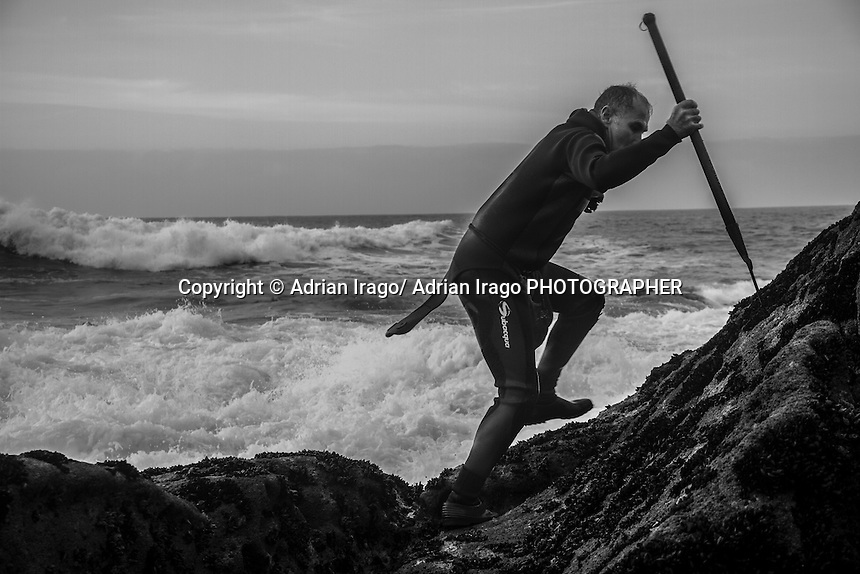 "A percebeiro climbing rocks to picking barnacle in Baiona on November 28, 2011 The art of shellfish in Galicia emerged as an alternative to poor and unprofitable agricultural economy. The seafood subsequently become the livelihood of the poorest peasants. Farmers moved techniques and tools plowing the rocks and beaches that make up the Galician coast in a survival exercise. With the passage of time and the achievement of a society with food needs covered what was once ""poor food"" today it is for the rich. © Adrián Irago"