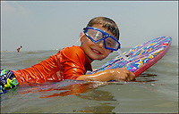 A young boy (model released) shows his muscles - and enthusiasm - at the beach Photo taken on Sullivan's Island, near Charleston, South Carolina beach on the Atlantic Ocean, but could represent a beach scene anywhere.