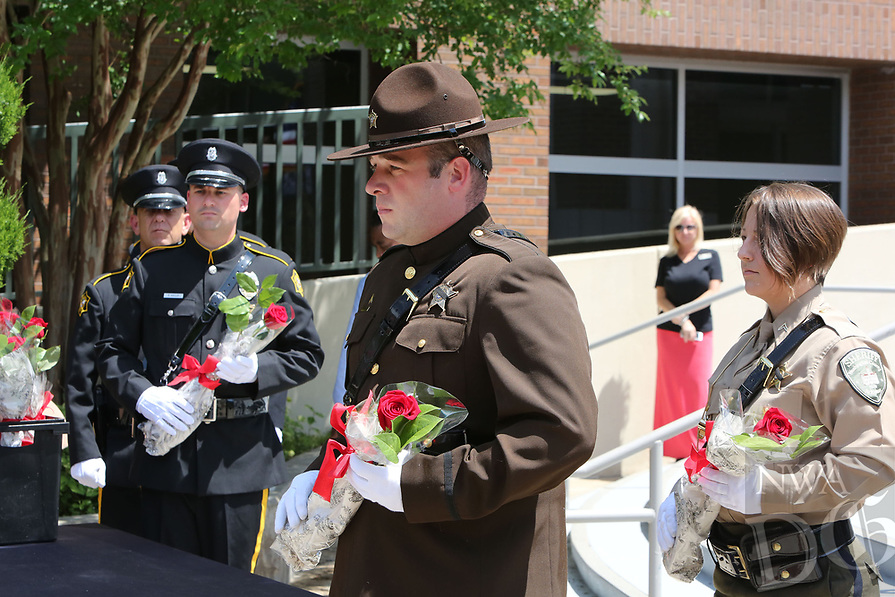 NWA Democrat-Gazette/DAVID GOTTSCHALK  Richard Bell, with the Law Enforcement Honor Guard,  prepares to hand out roses Monday, May 15, 2017, during the Northwest Arkansas Law Enforcement Memorial at the Town Center in Fayetteville.  Area law enforcement departments participated in the memorial that recognized officers from Northwest Arkansas who died in the line of duty.