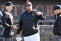 Head coach Landon Powell of the North Greenville Crusaders meets with umpires Mark Fitzgerald, left, and Josh Reep before a game against the Palm Beach Atlantic Sailfish on Monday, February 25, 2019, at Ashmore Park in Tigerville, South Carolina. Palm Beach won, 7-5. (Tom Priddy/Four Seam Images)