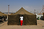 A man exits his tent in a special detention facility within Ketziot Prison compound, designated for African asylum seekers who have illegally crossed the nearby Egyptian border into Israel.