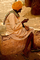 An Indian villager wearing traditional clothes rests at the village square in the hot afternoon.