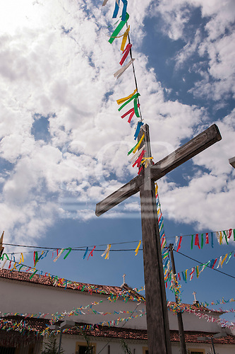Itaparica Island, Bahia State, Brazil. Itaparica town. Wooden cross with colourful bunting outside a colonial church. Blue sky and white clouds.