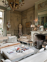 A formal sitting room with a central fireplace and, unusually, a concrete floor. The room is furnished with antique pieces in the Gustavian style.
