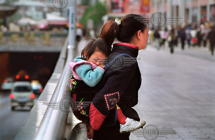 Ethnic minority mother carrying her child on her back...