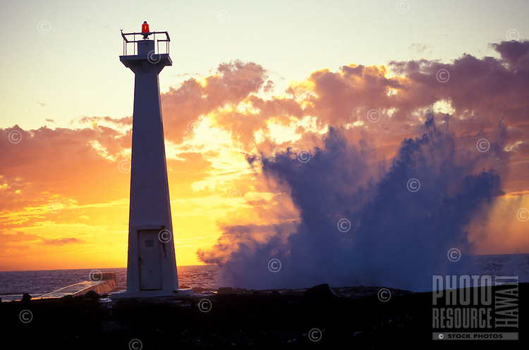Lighthouse and breaking waves at Keahole Point along the Kona coast at sunset