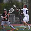 Matt Gavin #12 of Manhasset, right, snaps a shot past Joseph Tortorella #10, Carey goalie, during a Nassau County varsity boys lacrosse game at Manhasset High School on Wednesday, May 4, 2016. Gavin scored five goals in Manhasset's 14-6 win.