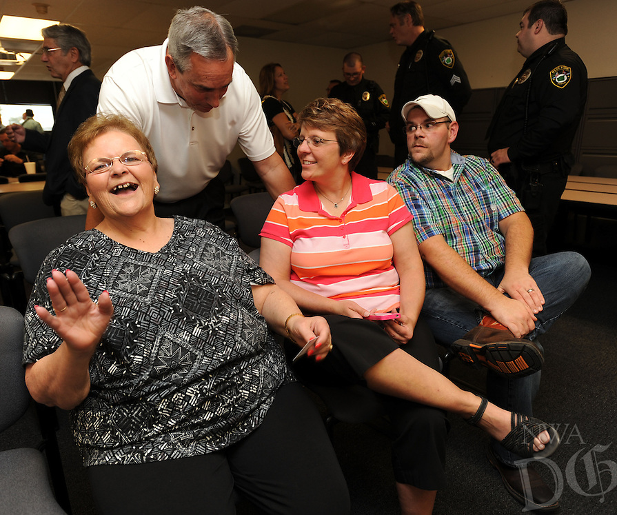 NWA Democrat-Gazette/ANDY SHUPE<br /> Greg Tabor (top), chief of the Fayetteville Police Department, speaks Wednesday, Sept. 2, 2015, with Myrrah Mueller of Farmington (left), her daughter, Paula Mueller and son, John Mueller, both of Prairie Grove, during a ceremony to award the Muellers with the American Police Hall of Fame Medal of Honor at the University of Arkansas Police Department in Fayetteville. Myrrah Mueller's husband, West Fork Police Chief Paul Mueller, was shot and killed on March 20, 1981, while making a traffic stop in West Fork following a robbery in Fayetteville.
