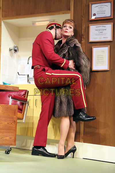 Samantha Bond.'What The Butler Saw' at the Vaudeville Theatre, The Strand, London, England..May 9th 2012.stage full length red uniform hat brown fur coat funny leg foot up kiss kissing .CAP/ROS.©Steve Ross/Capital Pictures