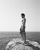 CROATIA, Dubrovnik, Dalmatian Coast, portrait of young man at Buza Bar, standing on rock before jumping into the ocean. The bar is located on the side of the cliff in Dubrovnik.