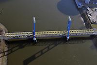 Kattwyk Bruecke: EUROPA, DEUTSCHLAND, HAMBURG, (EUROPE, GERMANY), 01.03.2013: Die Kattwyk Bruecke ueber der Suederelbe ist eine 290 Meter lange Hubbruecke mit zwei 70 m hohen Endportalen fuer den Eisenbahn- und Straßenverkehr. Sie verbindet Moorburg mit der Elbinsel Wilhelmsburg und wurde am 21. Maerz 1973 eingeweiht. Mit einer Hubhoehe von 46 m handelt es sich um die groesste Hubbruecke der Welt..Die Bruecke besteht aus zwei Trapezfachwerken ueber den Seitenoeffnungen und einem parallelgurtigen Fachwerkbalken ueber der Hauptoeffnung, der an 32 Stahlseilen aufgehaengt..Eine Besonderheit der Bruecke ist, dass die Eisenbahnschienen auf der Bruecke in der Mitte der Straßenfahrbahn verlaufen. Da sich Schienen- und Straßenverkehr die Kattwyk-Bruecke teilen, muss diese für die Durchfahrt eines Gueterzuges mittels Schrankenanlagen fuer den Straßenverkehr gesperrt werden. ..