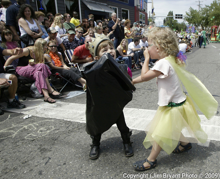Jasper Toms, right, and Jade Weston hold hands while marching in the 21st annual Summer Solstice Parade held Saturday, June 20, 2009 in Seattle, Wa. The parade was held Saturday, bringing out painted and naked bicyclists, bands, belly dancers and floats. (Jim Bryant Photo © 2009) .