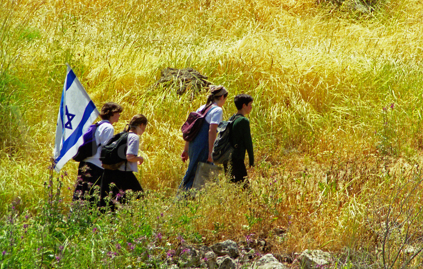 Four Israeli school children on a hike, carrying the Israeli flag.
