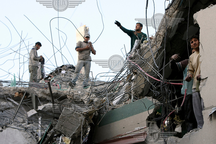 Workers begin the lengthy process of cleaning up the remains of the Hamas TV offices that were destroyed by an Israeli air strike in Gaza City. Israeli forces began an air offensive against Hamas in Gaza on 27/12/2008, which quickly escalated into an offensive by land, sea and air, in retaliation against Palestinian rockets fired into Israel.