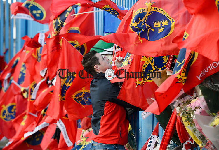 A fan fixes a Munster flag the gates of Thomond Park, in tribute to Munster and Ireland's Anthony Foley following his passing in France on Sunday. Photograph by John Kelly.