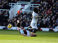 Pictured: Wilfried Bony of Swansea (R) is brought down by James Tomkins (L) of West Ham. 01 February 2014<br />