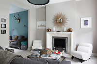 The living room in the narrow town house is furnished with flair and a subtle combination of tranquil colours