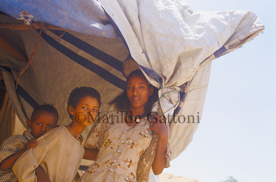 Eritrea - Debub- Family standing next to their tent in an IDP camp. As a result of 30 years of war for independence against Ethiopia (from 1961 to 1991) and another 3 years from 1997 to 2000, there are 50,000 Eritreans currently living in internally displaced (IDP) camps throughout the country. These IDPs have fled three times in the last 10 years, each time because of renewed military conflict. They lived in relatives' homes when lucky enough, but mostly, the fled to the mountains, where they attempted to do what Eritreans do best, survive. Currently there is no Ethiopian occupation in Eritrea, but landmines prevent the IDPs from finally going home. .It is estimated that every Eritrean family lost two or three members to the war which makes the reality of the current emergency situation even more painful for Eritreans worldwide. Currently, the male population has been decreased dramatically, affecting the most fundamental socio-economic systems in the country. Among the refugee population, an overwhelming majority of families are female-headed, severely affecting agricultural production. For, IDPs in particular, 80% of households are female-headed..The unresolved border dispute with Ethiopia remains the most important drawback to Eritrea's socio-economic development, as national resources (human and material) continue to be prioritized for national defense. Eritrea is vulnerable to recurrent droughts and variable weather conditions with potentially negative effects on the 80 percent of the population that depend on agriculture and pastoralism as main sources of livelihood. The situation has been exacerbated by the unresolved border dispute, resulting in economic stagnation, lack of food security and increased susceptibility of the population to various ailments including communicable diseases and malnutrition..