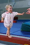 Albany, Ca Girl, eighteen months old, walking on balance beam in gymnastics program for preschool children about to be grabbed by father's hand  MR
