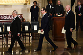 Acting Attorney General, Matthew Whitaker (R), Secretary of the Treasury, Steven Mnuchin (C), and Secretary of Defence James Mattis walk through the rotunda before the casket containing the remains of former US President George H.W. Bus arrives at the US Capitol during a State Funeral in Washington, DC, December 3, 2018. - The body of the late former President George H.W. Bush will travel from Houston to Washington, where he will lie in state at the US Capitol through Wednesday morning. Bush, who died on November 30, will return to Houston for his funeral on Thursday. (Photo by Brendan SMIALOWSKI / AFP)