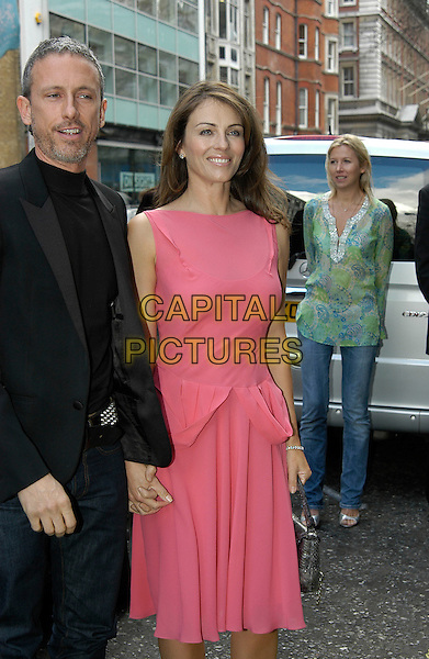 PATRICK COX & ELIZABETH HURLEY.Attend the VIP Ad Campaign Lunch in celebration of designer Patrick Cox's latest ad campaign that Elizabeth Hurley fronts at the Sanderson Hotel, London, UK..February 14th, 2006.Ref: IA.half length pink dress sleeveless holdimg hands.www.capitalpictures.com.sales@capitalpictures.com.©Capital Pictures