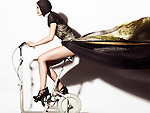 Young woman in a beautiful flying in the wind long dress posing on a retro exercise bike. Edgy high fashion photo.
