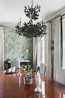 A contemporary chandelier of metal oak leaves is a distinctive yet not overwhelming feature of this dining room