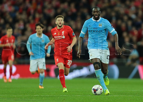 28.02.2016. Wembley Stadium, London, England. Capital One Cup Final. Manchester City versus Liverpool. Manchester City Midfielder Yaya Touré brings the ball forward as Liverpool Midfielder Adam Lallana chases
