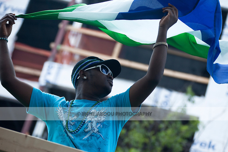 A man waves the flag of Sierra Leone, a war-torn country in West Africa, at the DC Caribbean Carnival.  Launched by a large Caribbean-style parade with dancers in traditional Caribbean carnival costumes, the festival promotes and educates the community about Caribbean arts, crafts, and culture.