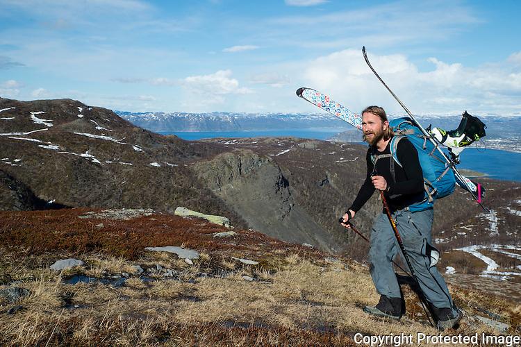 Mann bærer ski på ryggen på vei mot Halddetoppen ved Alta. ---- Man carrying skis towards Haldde.