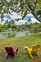 Two chairs overlooking boat and swan on pond at Smith's Tropical Gardens. Kauai, Hawaii